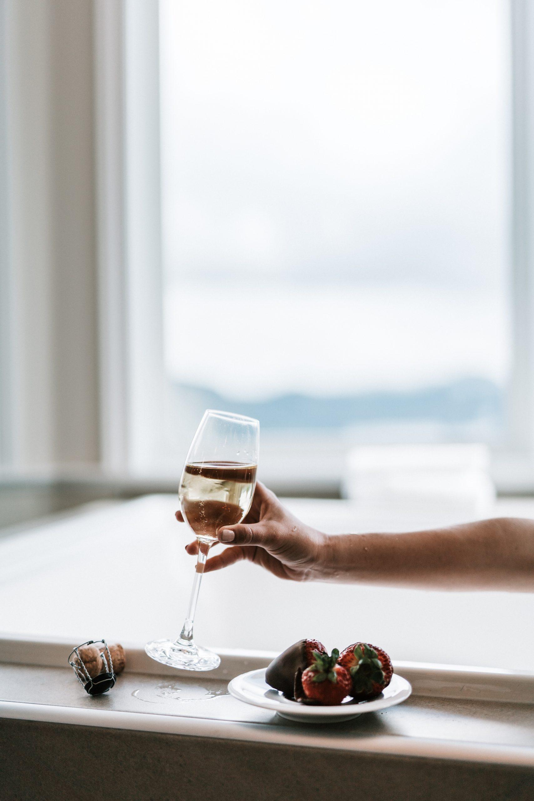 En la foto, una copa de vino y fresas con chocolate. /Foto: Pexels