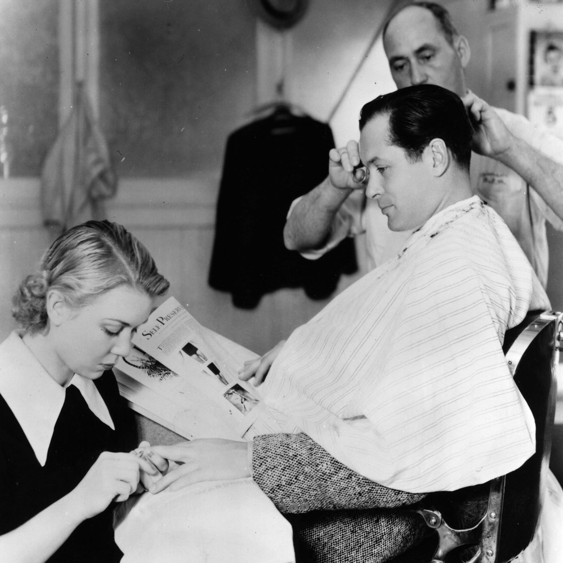 circa 1933: Robert Montgomery, the Hollywood star, signed by MGM, seen having a trim and manicure in the studio barber shop. (Photo by Hulton Archive/Getty Images)