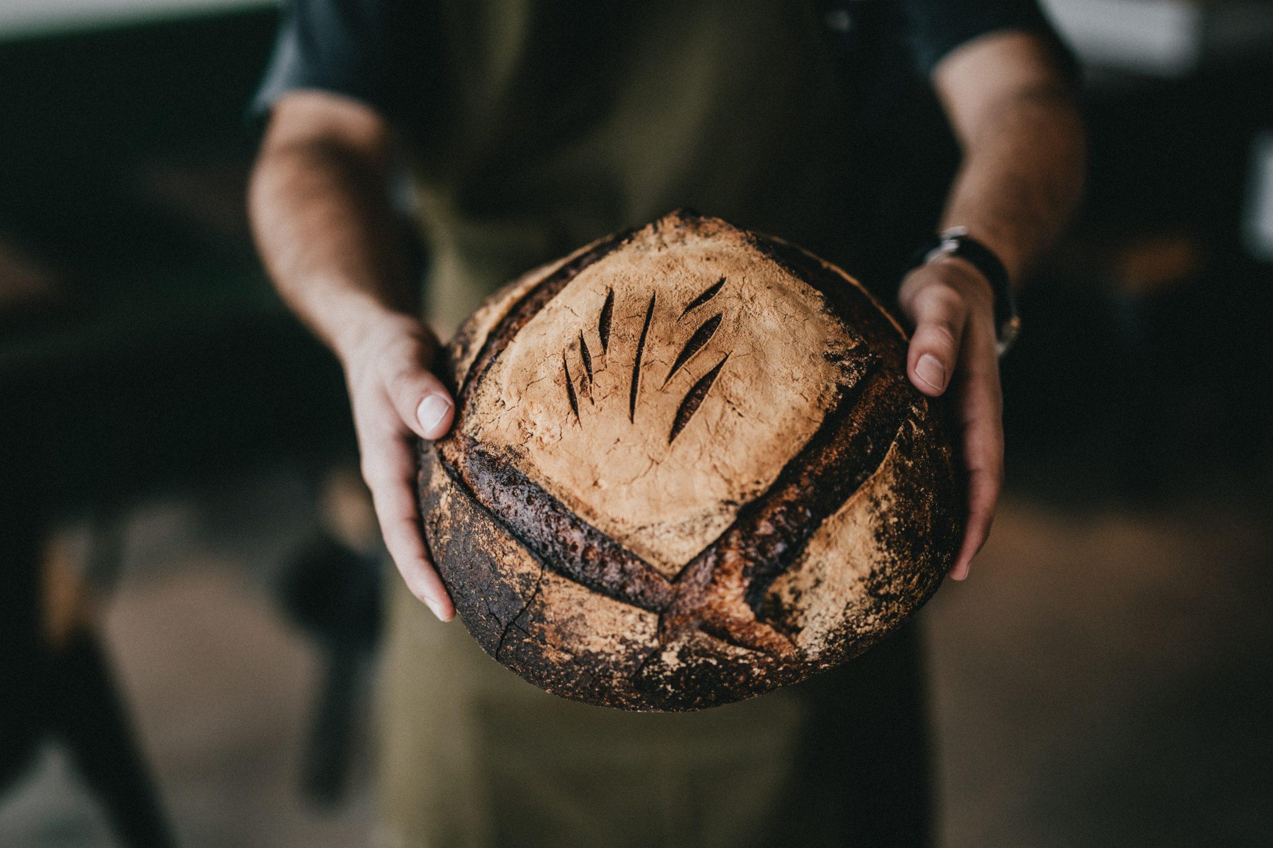 En la imagen, un panadero presentando el producto recién hecho. /Foto: Unsplash