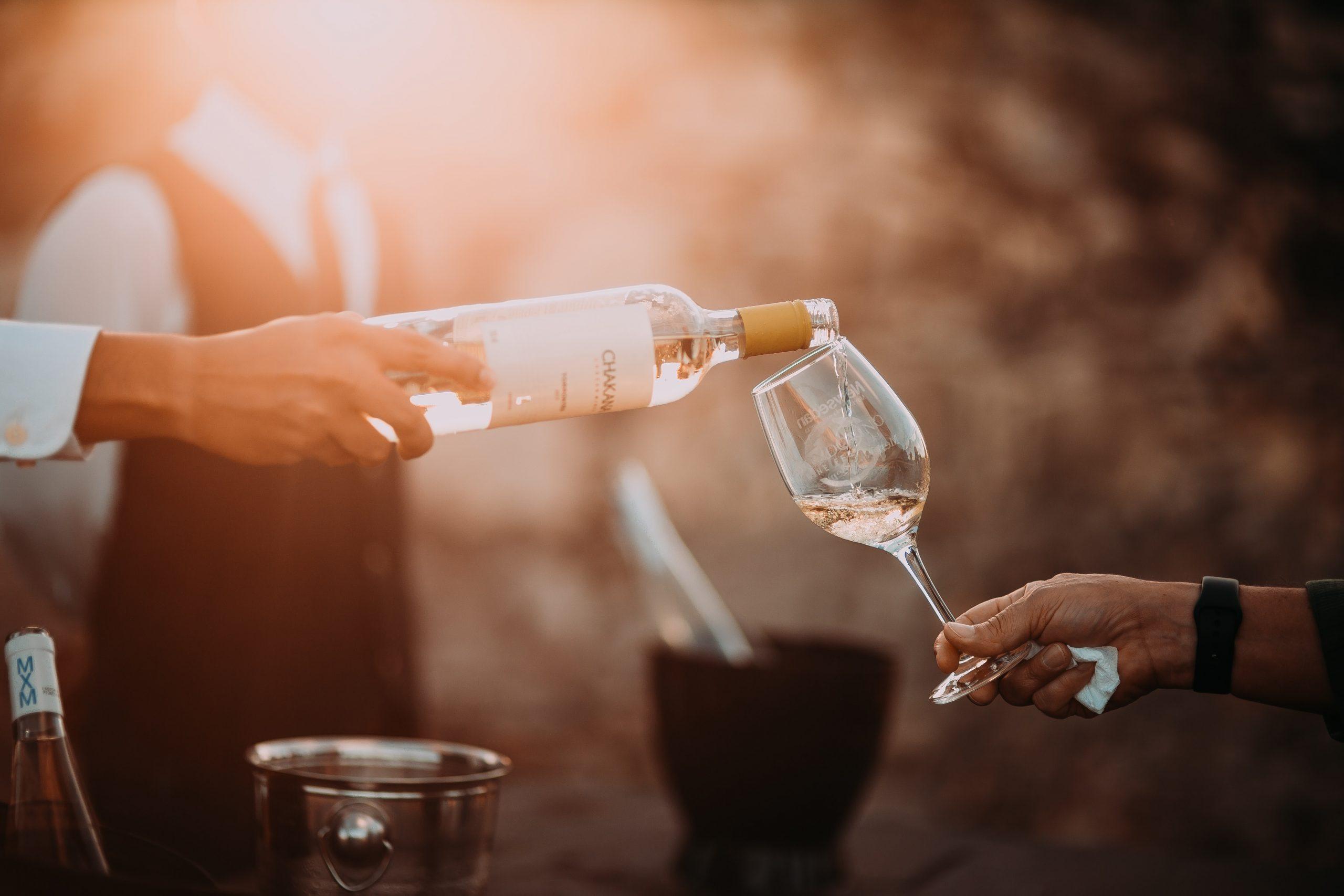 En la imagen, una pareja se sirve una copa de vino. /Foto: Unsplash