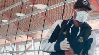 Thompkins, con mascarilla y guantes antes de viajar a Milán.