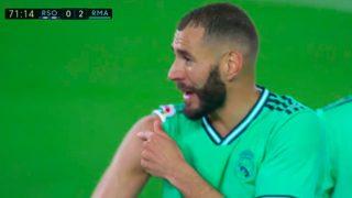 Benzema explica al árbitro que controla el balón con el hombro.