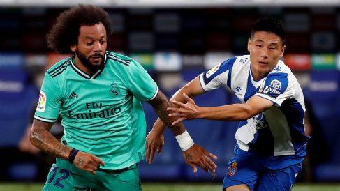 Marcelo y Wu Lei disputan un balón. (EFE)