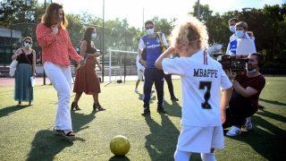 La ministra juega con una niña con una camiseta de Mbappé.