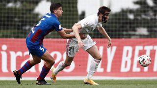 Latasa agarrado por un jugador del Poblense durante el partido. (realmadrid.com)
