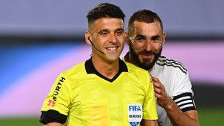 Gil Manzano y Karim Benzema, durante un partido del Real Madrid la pasada temporada. (AFP)