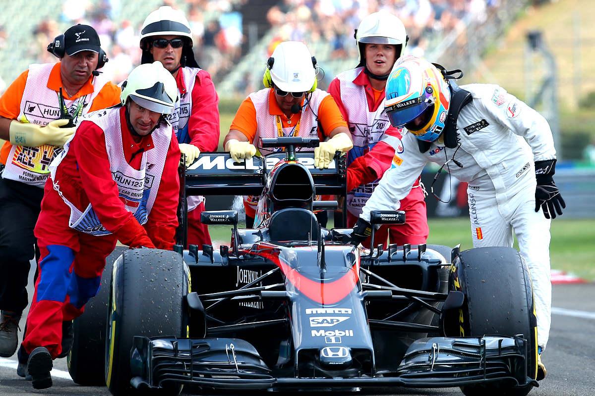 Fernando Alonso remolca su coche en un Gran Premio, una imagen habitual esta temporada.