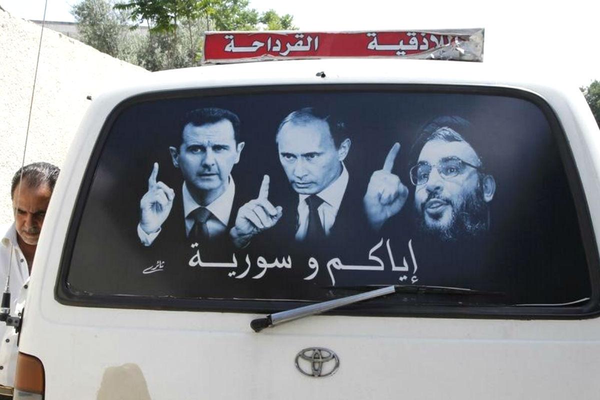 Un cartel que muestra al presidente sirio, Bashar el Asad (I), al ruso, Vladimir Putin, y al líder de Hezbolá, Sayed Hasan Nasralá en un microbus en al-Qardahah, cerca de Latakia. (REUTERS/Khaled al-Hariri)