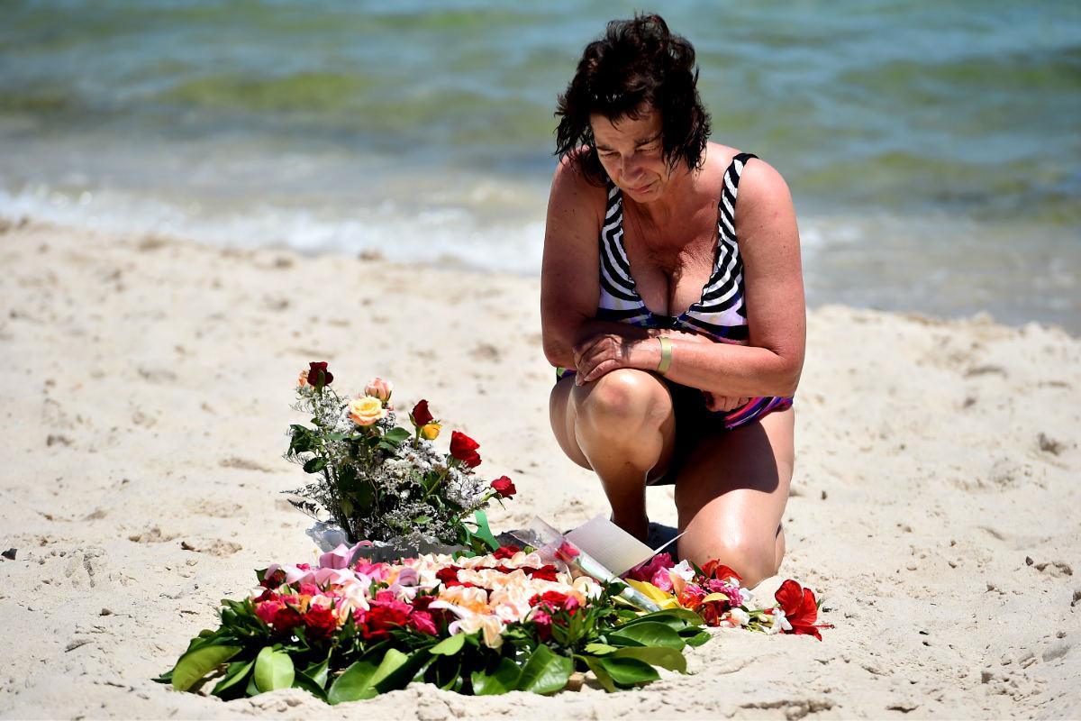 Una turista deja un ramo de flores sobre la arena de la playa donde fueron asesinados 37 turistas (Foto: Getty)