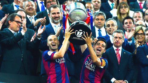 Iniesta y Xavi Hernández levantan la Copa del Rey con el Rey Felipe VI de fondo. (Getty)