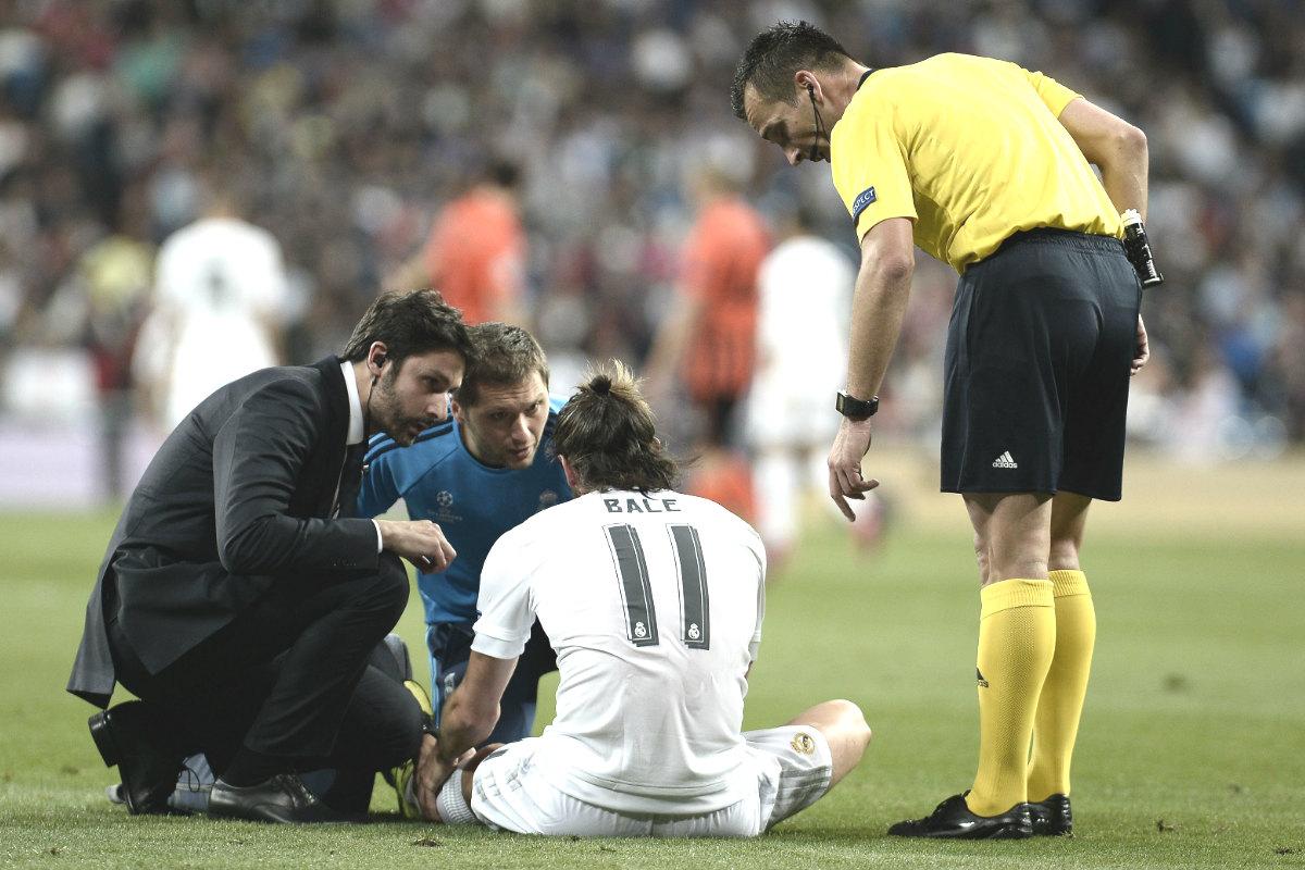 Bale, sentado en el césped, explica a los fisios su lesión ante el Shakthar. (Getty)
