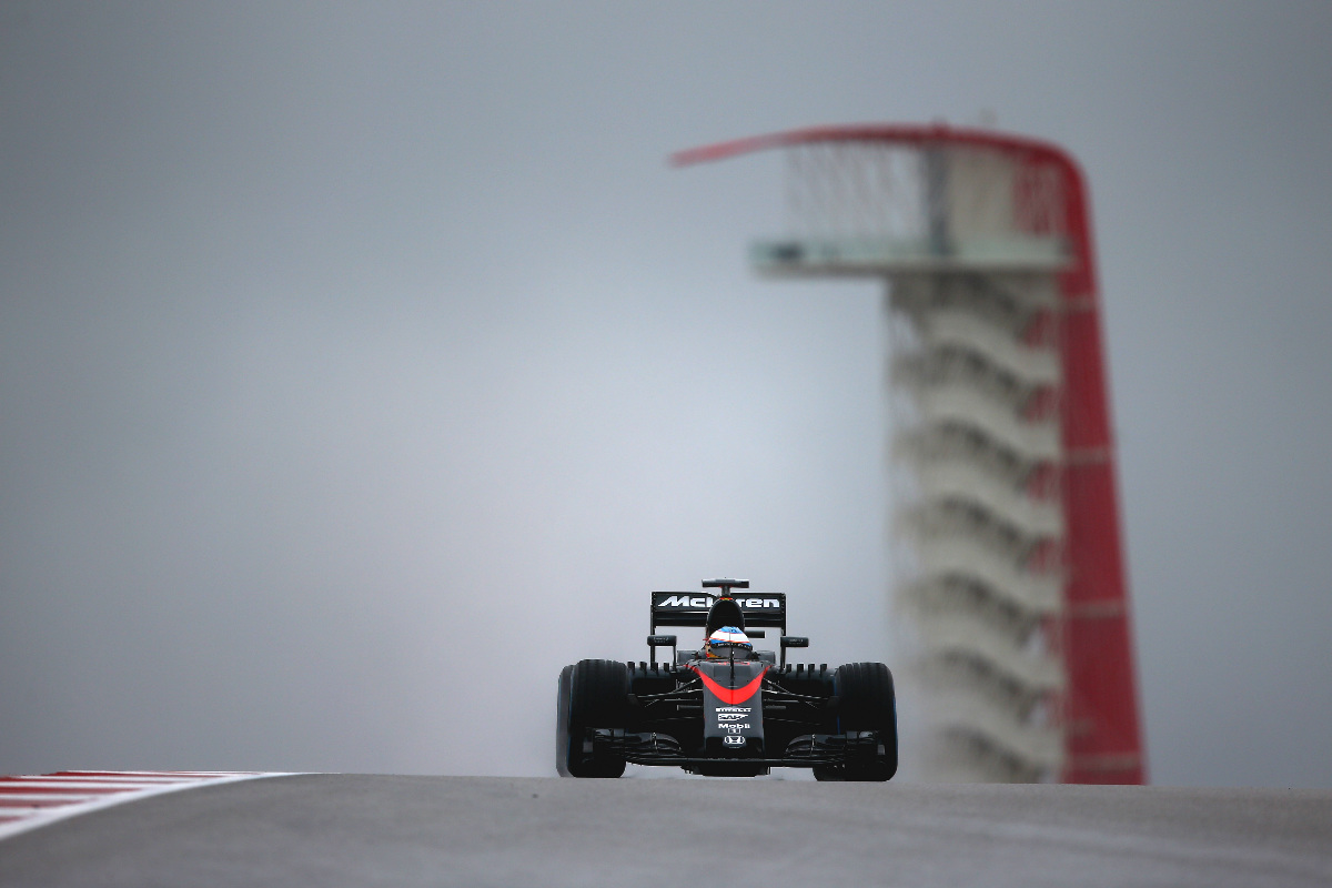 Fernando Alonso levanta una nube de agua en una recta.