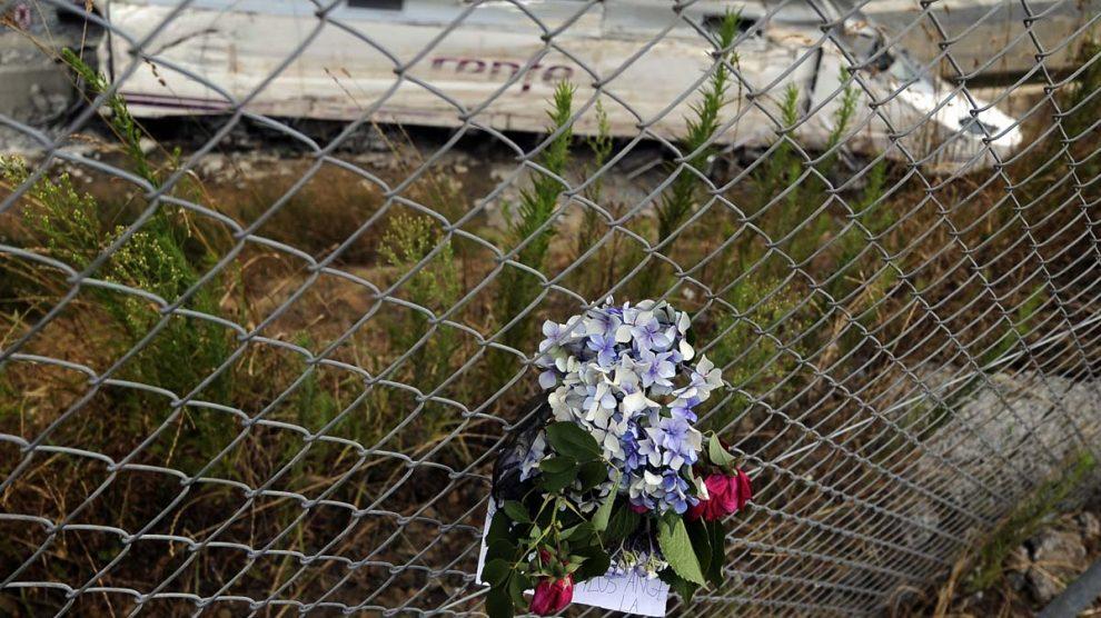 Un ramo de flores ante al máquina accidentada del Alvia en Angrois. (Foto: AFP)