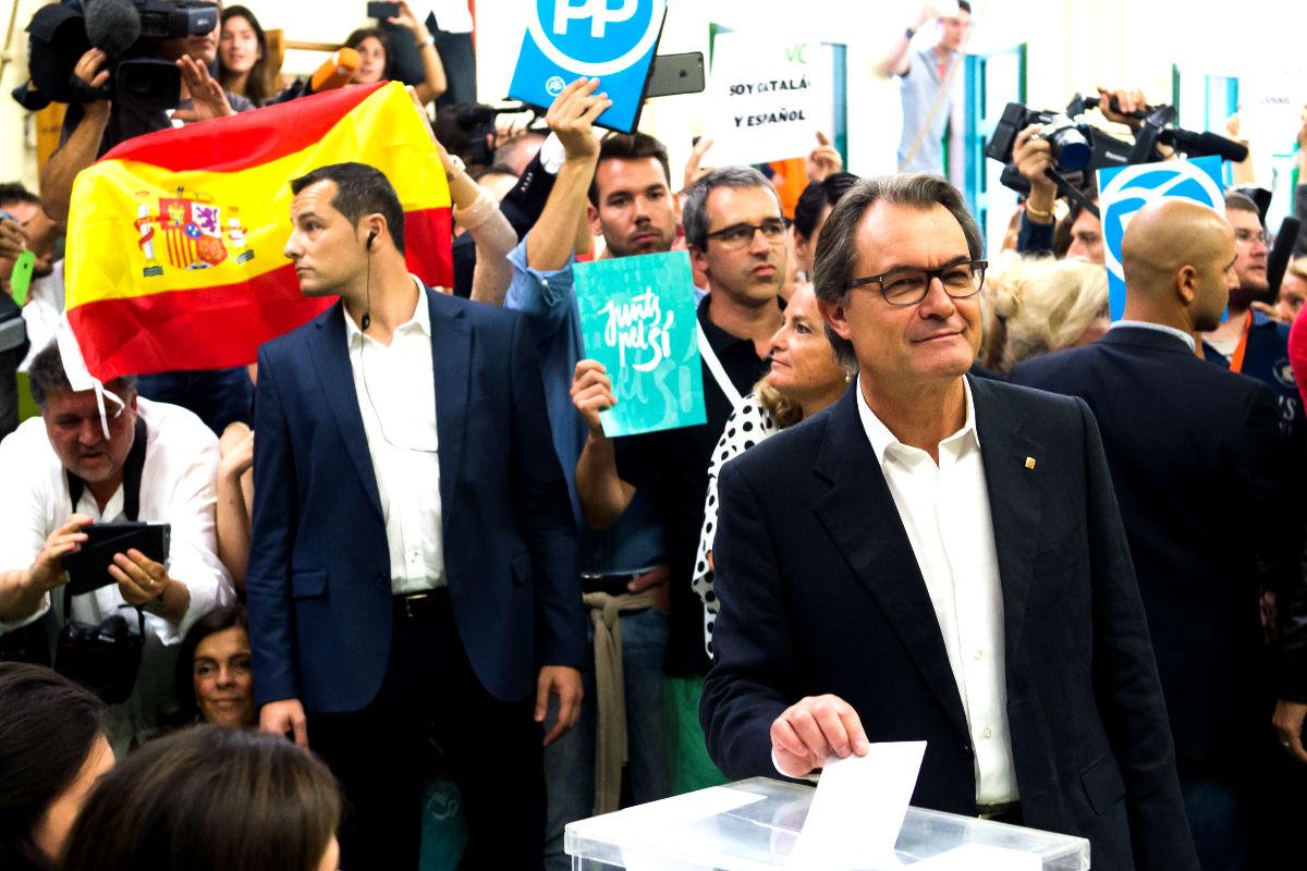 Exhiben una bandera española mientras Artur Mas vota en las elecciones del 27S (Foto: Getty)