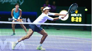 Garbiñe Muguruza, con Carla Suárez al fondo, volea en las semifinales del Masters. (Getty)
