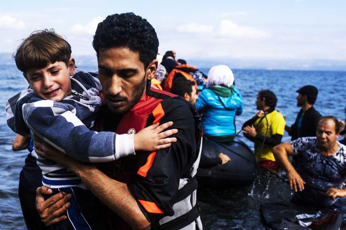 Un padre sostiene a su hijo tras desembarcar en las isla de Lesbos (Grecia). (Foto: AFP)