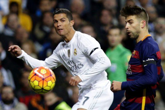 El delantero portugués del Real Madrid, Cristiano Ronaldo, disputa el balón con el defensa del FC Barcelona Gerard Piqué, en el partido de la jornada 12º de liga de Primera División que les enfrenta en el Estadio Santiago Bernabéu. EFE