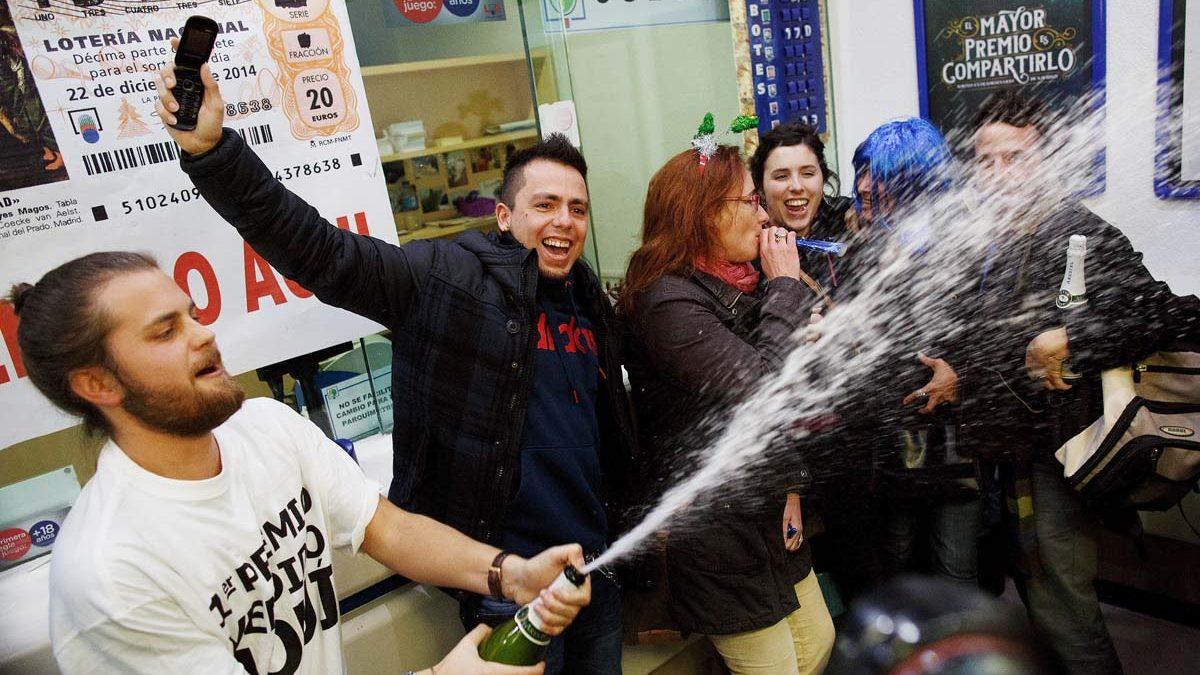 Varios agraciados con un premio de la Lotería de Navidad lo celebran en una administración. (Foto: Getty)