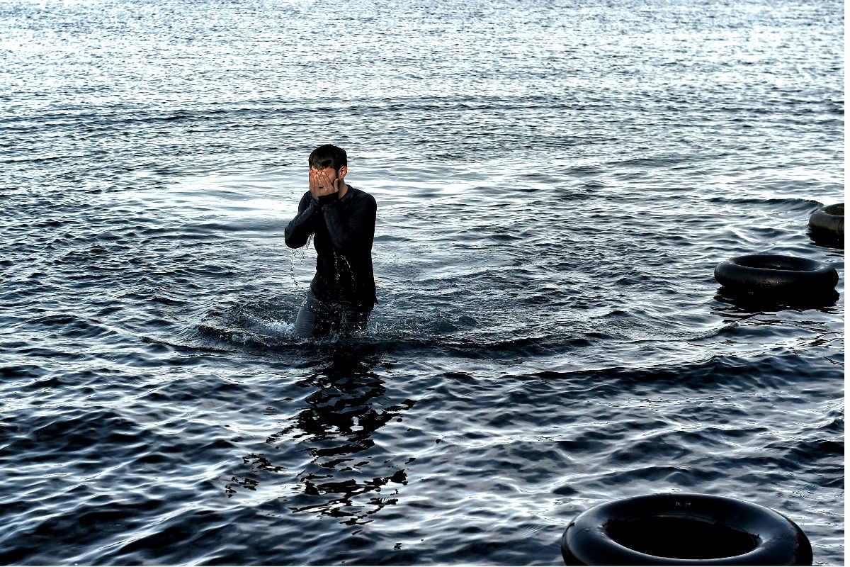 Un hombre camina entre el agua a su llegada a la isla de Lesbos. (Foto: AFP)