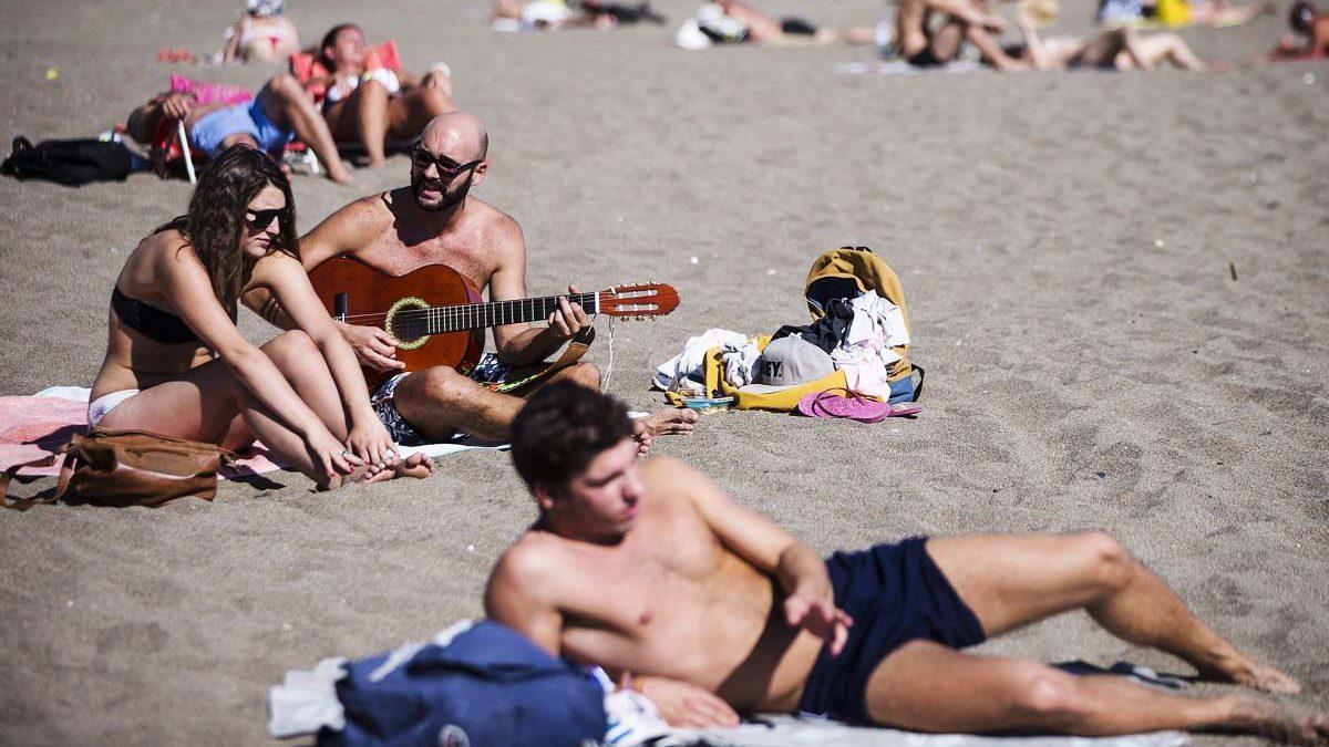 Varias personas toman el sol en la playa de la Malagueta. (Foto: EFE)