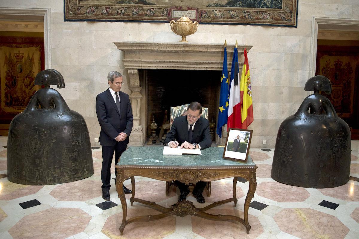 El presidente Mariano Rajoy firma, hoy sábado, en el libro de condolencias instalado en la embajada de Francia en Madrid (Foto: Efe)