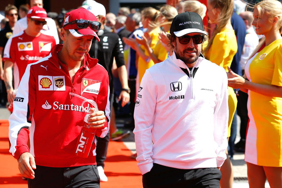 Fernando Alonso pasea por la parrilla junto a Sebastian Vettel.