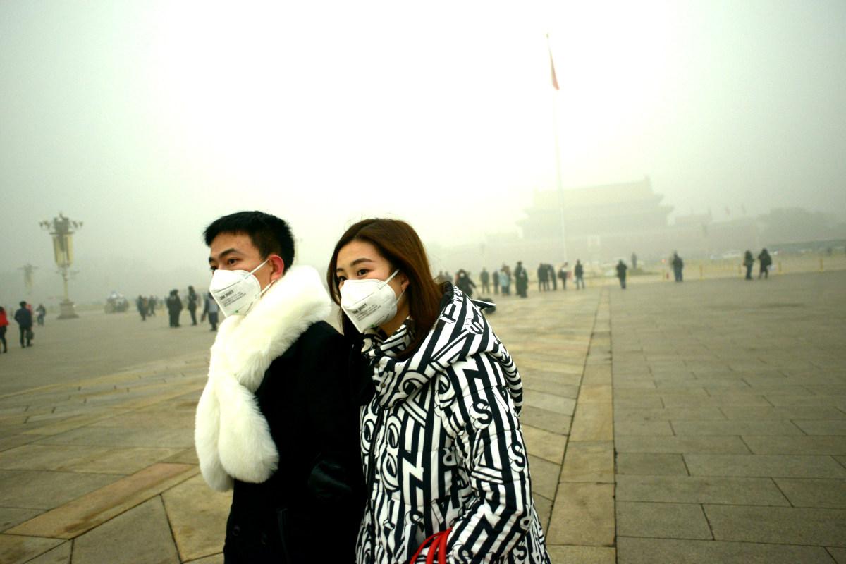 Una pareja lleva máscaras mientras pasea por la plaza de Tianammen. (Foto: AFP)