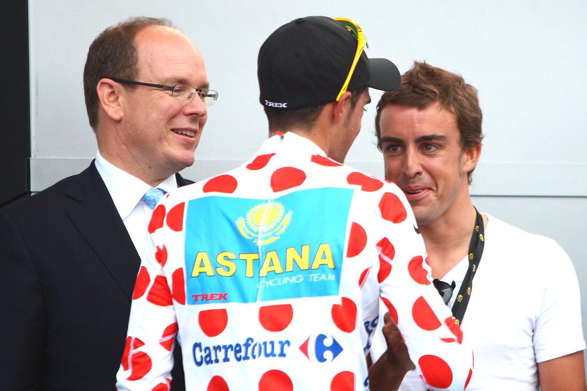Alberto Contador conversa con Fernando Alonso en el podio del Tour de Francia.