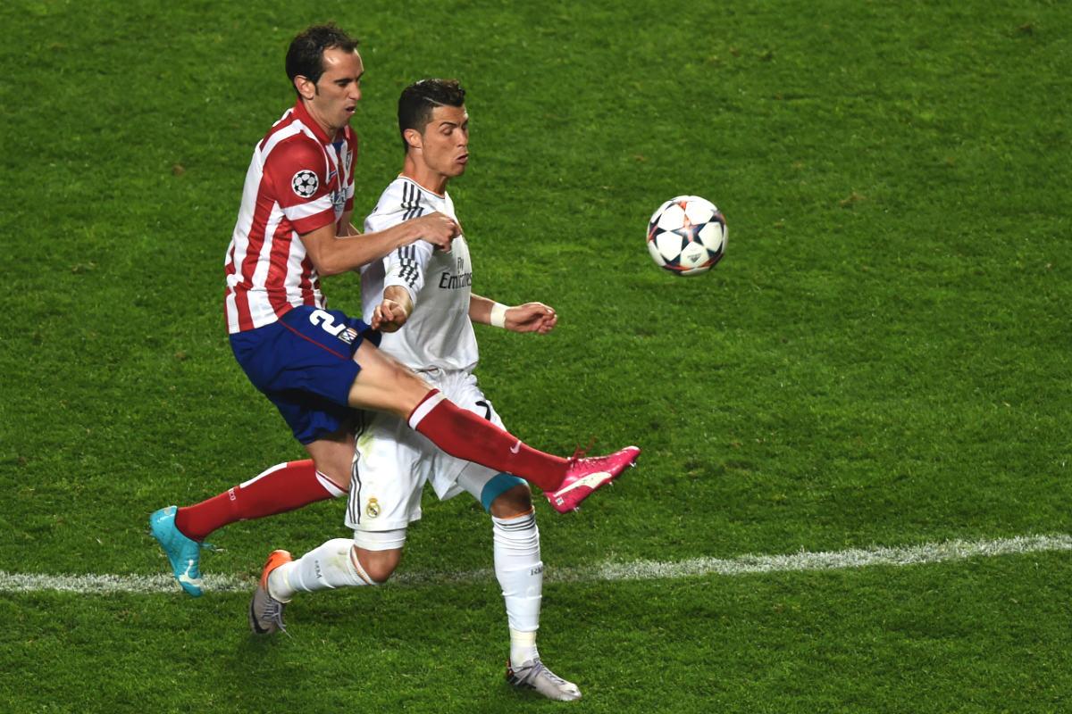Godín disputa un balón con Cristiano en la final de Lisboa. (AFP)