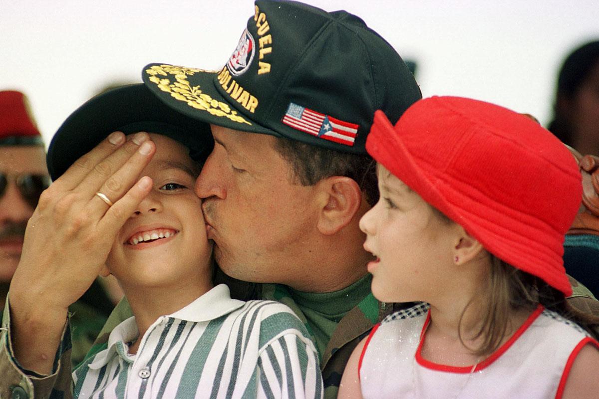 Chávez besando a un niño durante un acto militar en Puerto de Guaira. (Foto: AFP)