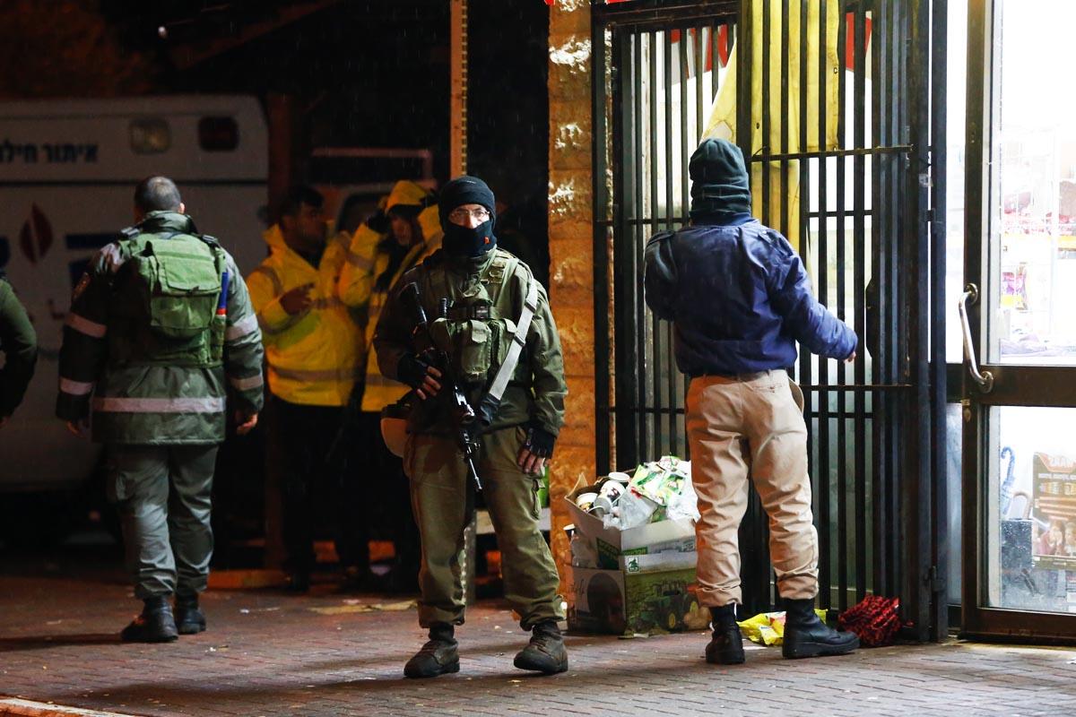 Miembros de las fuerzas de seguridad israelíes a la puerta del establecimiento donde se produjo la agresión. (Foto: AFP)