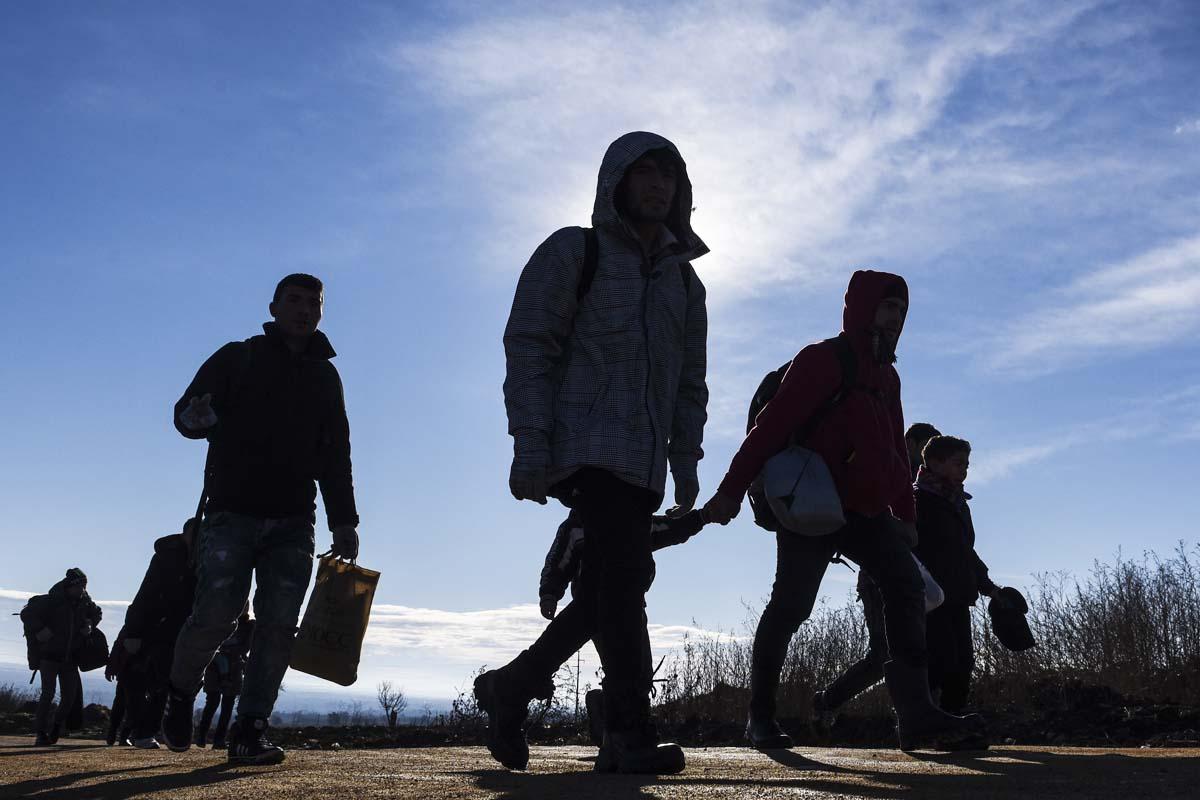 Imagen de unos refugiados caminando por medio de un campo. (Foto: AFP)