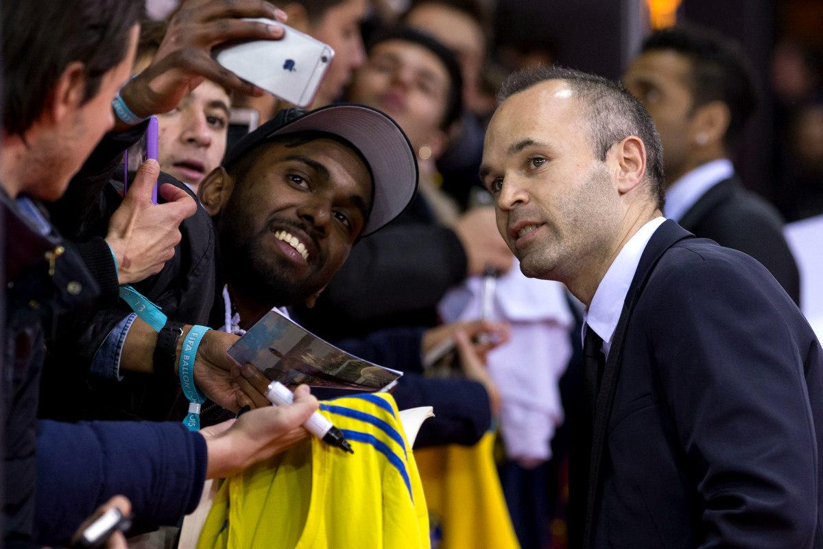 Andrés Iniesta se hace una foto con los aficionados a la entrada de la gala Balón de Oro.