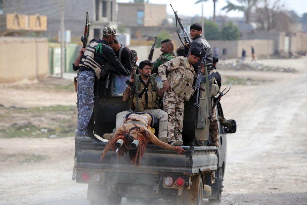 Fuerzas iraquíes trasladan el cadáver de un identificado como miembro del ISIS. (Foto: AFP