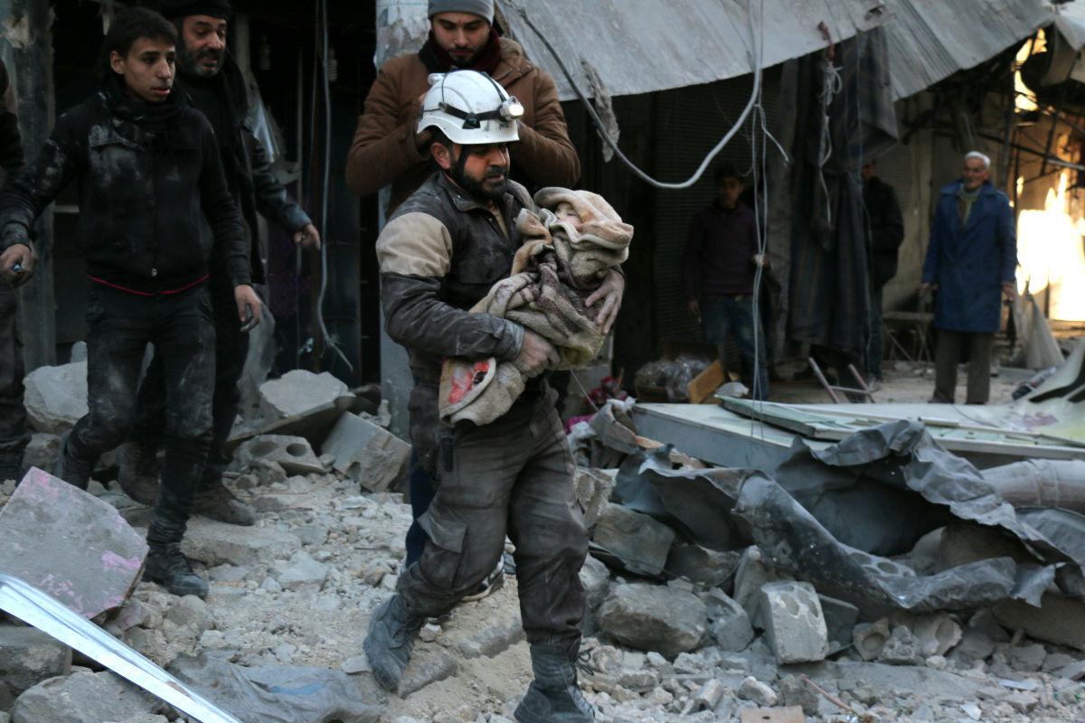 Un hombre rescata a un niño tras el ataque del Estado Islámico (Foto: Efe).