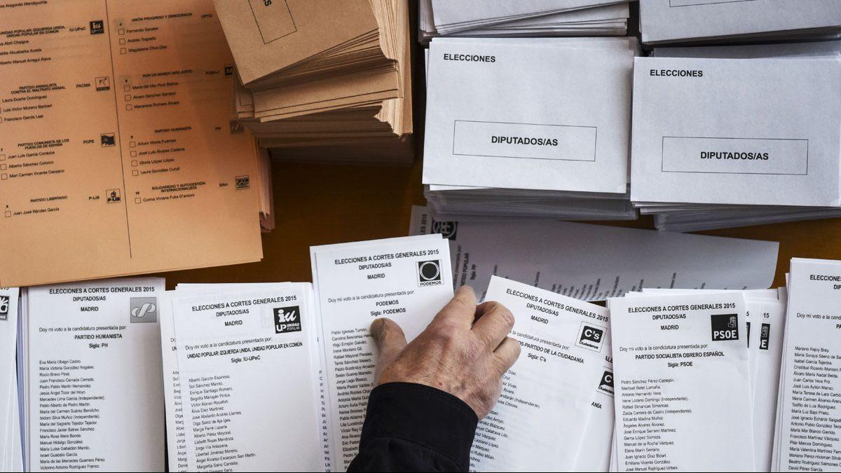 Un votante coge la papeleta en un colegio electoral en el 26J. (Foto: AFP)