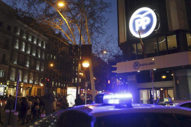 Un coche de la Policía, aparcado ante la sede del PP en Madrid, este jueves. (Foto: EFE)