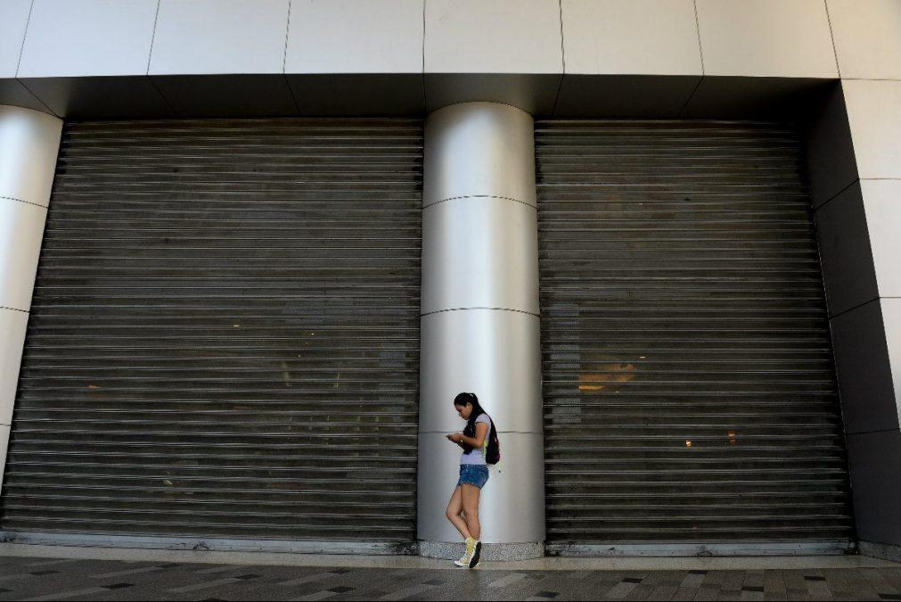 Una joven frente a las puertas cerradas de un centro comercial. (Foto: AFP)