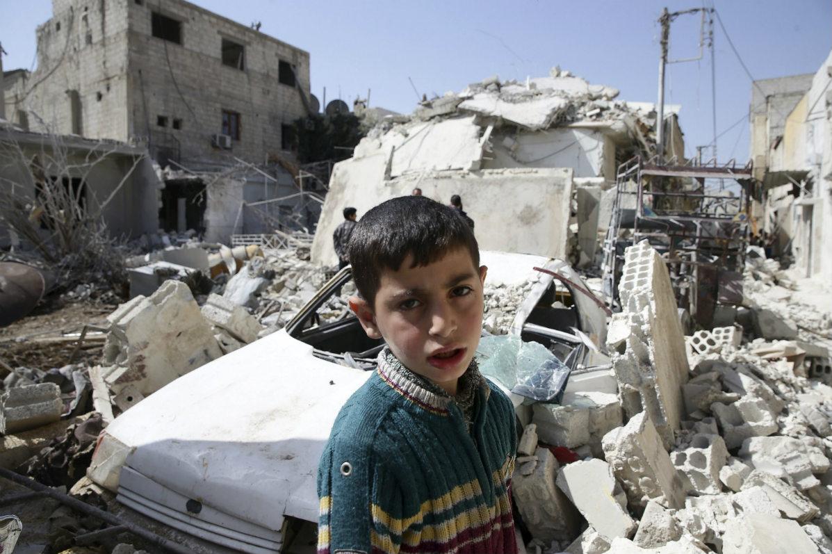 Un niño, junto a varios edificios derruidos por el bombardeo en Douma, Damasco. (Reuters)