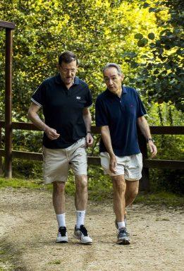 Mariano Rajoy caminando en verano junto a José Benito Suárez, marido de Ana Pastor. (Foto: EFE)