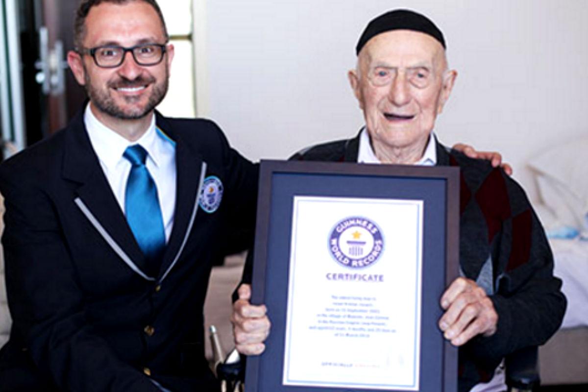 Israel Kristal sosteniendo su título de hombre más viejo del mundo otorgado por Marco Frigatti, director de los Records Guinness.