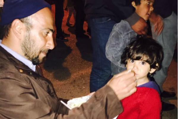 Un refugiado alimenta a su hijo, Anone, en un campo de refugiados en El Pireo. (AMC)