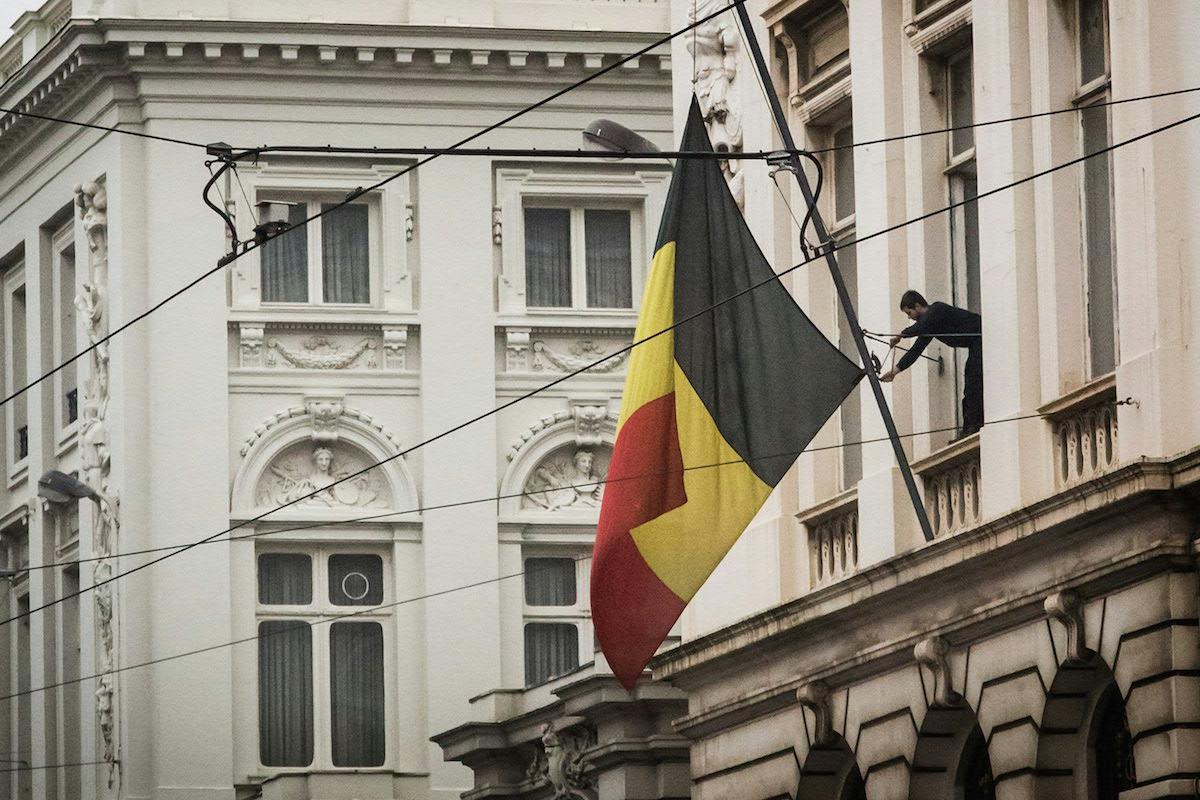 Un funcionario coloca la bandera belga a media hasta en el Palacio Real. (Foto: AFP)