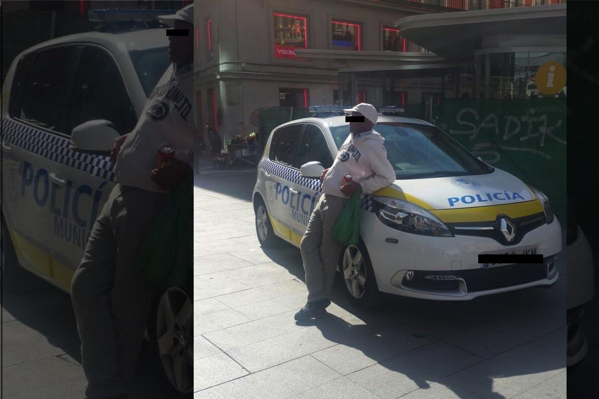 Vendedor ilegal sobre un coche policial. (Foto: OKDIARIO)