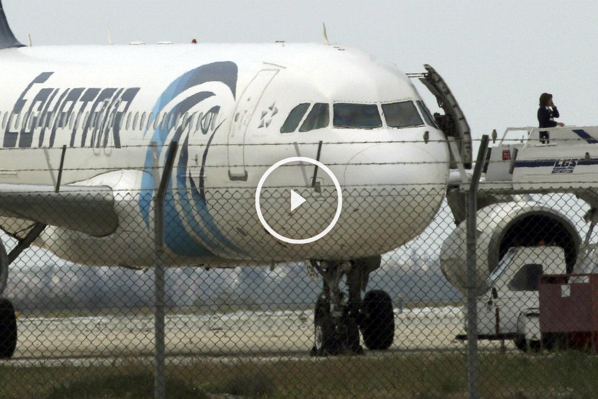 Una funcionaria habla por teléfono en las escalerillas del avión secuestrado de Egytair en el aeropuerto de Larnaca, Chipre. (Reuters)
