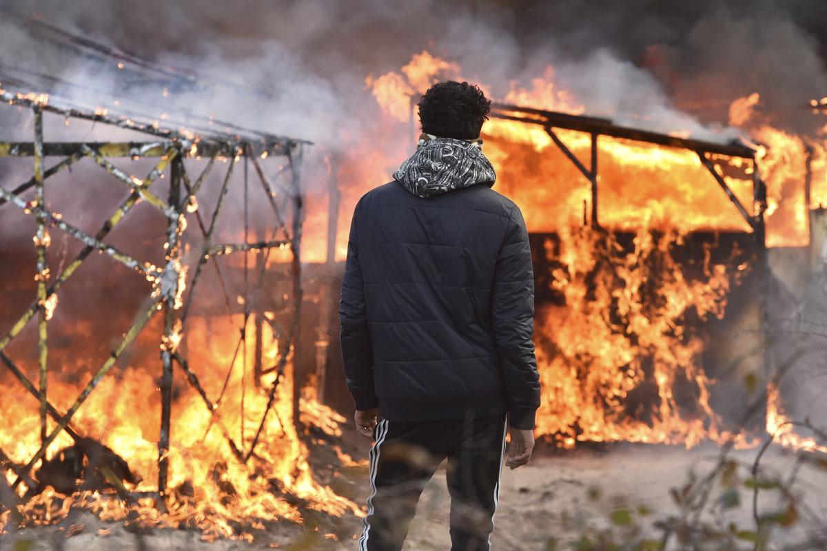 Un migrante observa cómo arde el campamento. (Foto: AFP)