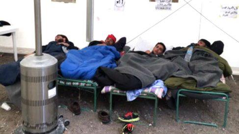 Tres refugiados intentan descansar en el campamento de Gizona.