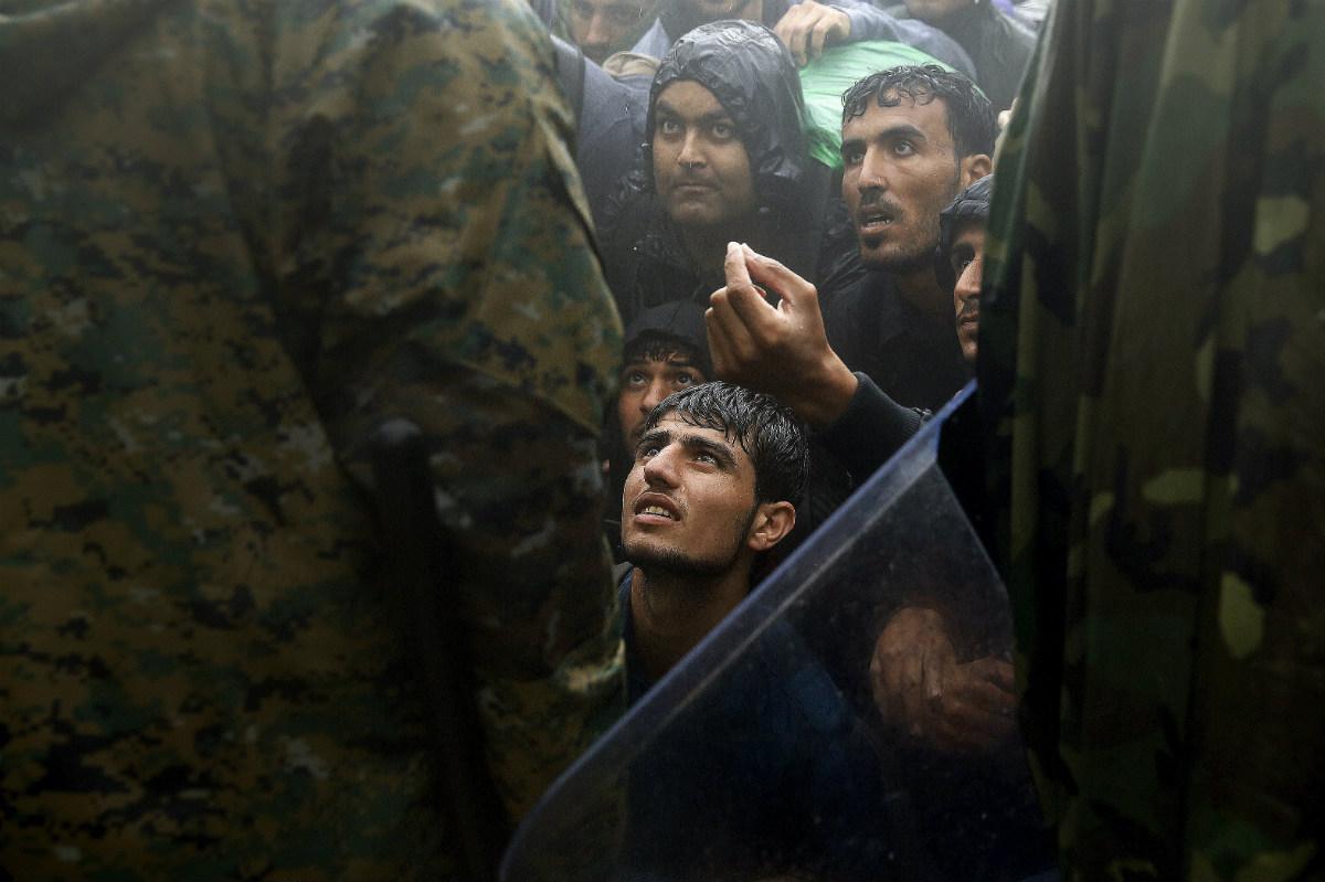 Migrantes sirios suplican a la policía que les cierra el paso en la frontera griega de Idomeni con Eslovenia. (Reuters)