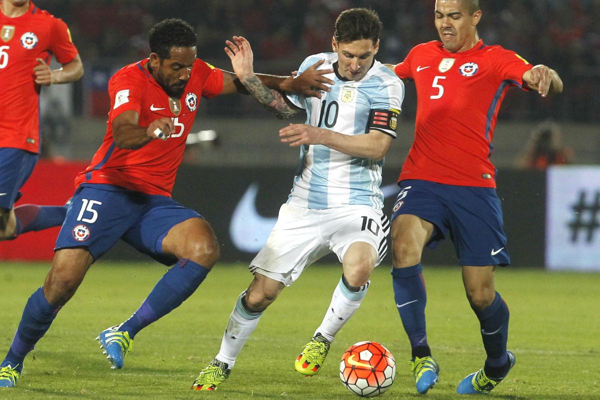 Messi intenta regatear a dos jugadores de Chile. (AFP)