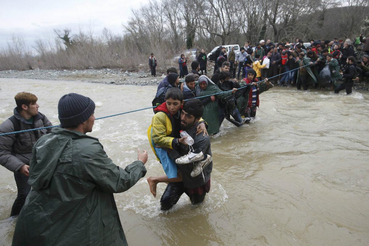 Decenas de refugiados tratan de pasar a Macedonia desde Grecia vadeando el río Suva Reka. (Reuters)